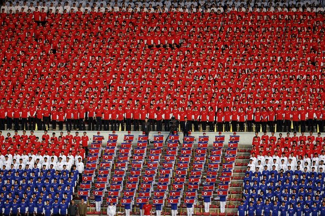 North Korean fans in national colours sing their national anthem before their team's preliminary 2018 World Cup and 2019 AFC Asian Cup qualifying soccer match against Philippines at the Kim Il Sung Stadium in Pyongyang October 8, 2015. (Photo by Damir Sagolj/Reuters)