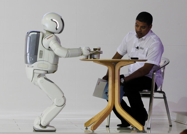 ASIMO, a humanoid robot created by Honda, serves tea to a visitor during the Johannesburg International Motor Show at Nasrec in Johannesburg, October 6 2011. (Photo by Siphiwe Sibeko/Reuters)