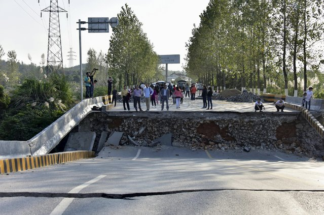 People look on near a section of a bridge which has collapsed, in Chibi, Hubei province, China, October 11, 2015. The bridge collapse which occurred on Sunday morning has blocked a street, and is currently being repaired. No casualties have been reported, according to local media. (Photo by Reuters/China Daily)