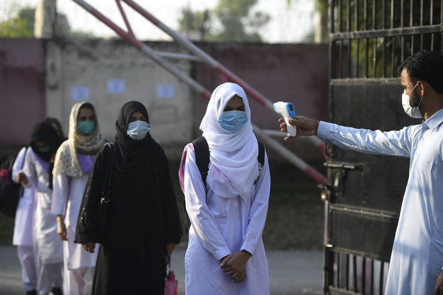 A staff member checks the body temperature of students at the entrance of the Islamabad Model College of Commerce for Girls in Islamabad on September 15, 2020 after the educational institutes were reopened nearly six months after the spread of the Covid-19 coronavirus. (Photo by Aamir Qureshi/AFP Photo)
