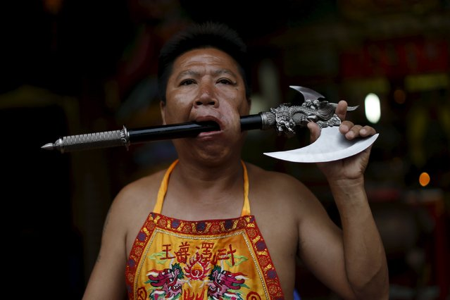 A devotee of the Chinese Bang Neow shrine sits with an axe pierced through his cheek during a procession celebrating the annual vegetarian festival in Phuket, Thailand October 18, 2015. (Photo by Jorge Silva/Reuters)