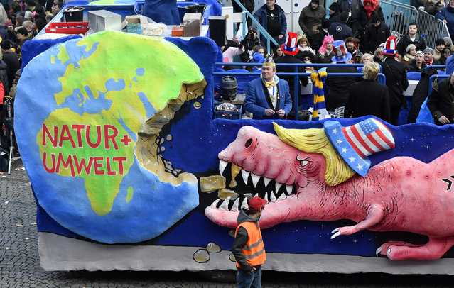 A carnival float depicts a dinosaur with the U.S. flag on its hat eating a large chunk from the earth during the traditional Rose Monday parade in Duesseldorf, Germany, Shrove Monday, February 12, 2018. (Photo by Martin Meissner/AP Photo)