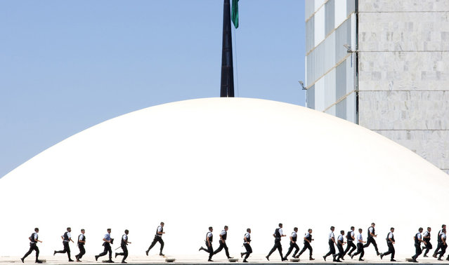 """Policemen Run Across the National Congress in Brasília During a Demonstration Against Corruption"". Photo by Olivier Boëls (Brasilia, Brazil). Photographed in Brasilia, Brazil, September 2011."