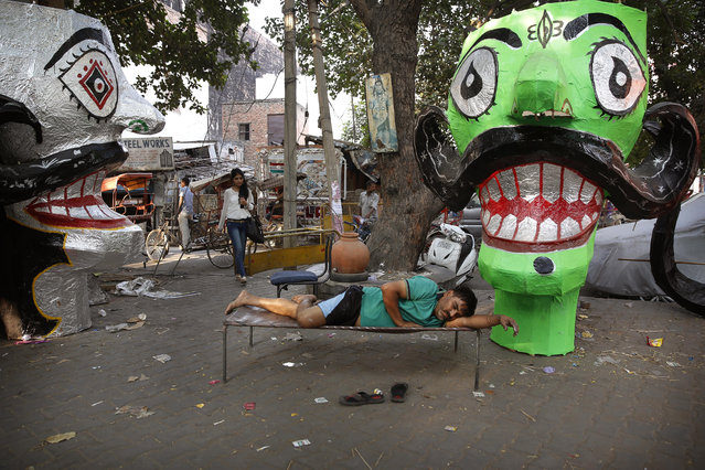 An Indian artist rests on a cot after preparing effigies of the ten-headed demon god Ravana in preparation for the upcoming Dessehra festival in New Delhi, India, Tuesday, October 20, 2015. Dussehra, also known as Vijayadashami, commemorates the victory of the Hindu god Rama over Ravana, an evil ruler who had abducted Rama's wife, Sita Devi. (Photo by Manish Swarup/AP Photo)