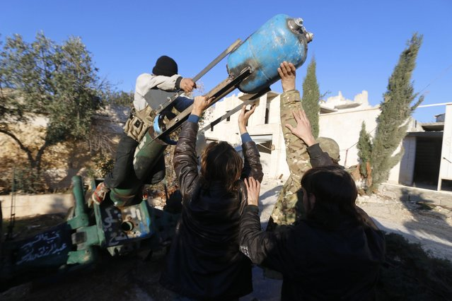 Fighters from the Noureddine Zanki movement, which operates under the Free Syrian Army, prepare an improvised explosive to fire towards forces loyal to Syria's President Bashar al-Assad at the frontline in Aleppo's al-Rashideen neighbourhood November 27, 2014. (Photo by Hosam Katan/Reuters)