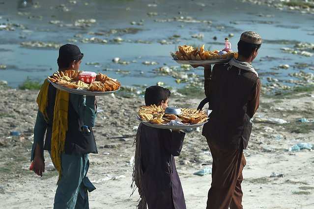 Samosa vendors walk as they look for customers at the Shuhada Lake in Kabul on September 1, 2020. (Photo by Wakil Kohsar/AFP Photo)