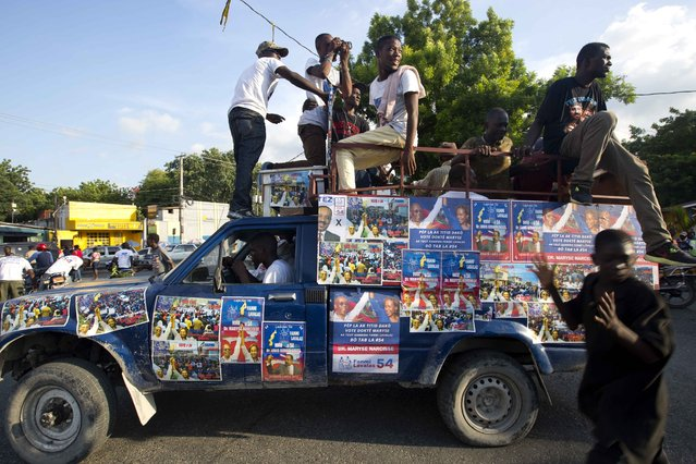 In this September 21, 2016 photo, a truck is covered with campaign signs in favor of Haiti's former President Jean-Bertrand Aristide and presidential candidate Maryse Narcisse, of the Fanmi Lavalas political party, during a campaign event in Port-au-Prince, Haiti. (Photo by Dieu Nalio Chery/AP Photo)