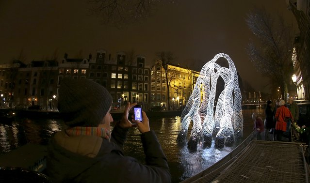 """In this Saturday, November 29, 2014 photo, a man takes a picture of the """"Arborescence"""" light sculpture by Britain's Loop.pH, as it floats in Herengracht Canal in Amsterdam. The sculpture is a playful part of the Amsterdam Light Festival which opened November 27, 2014. In a giant open air exhibition that lasts until Jan. 18, the waterways and web of canals that make up the historic heart of Amsterdam, form a backdrop for dozens of works of art. (Photo by Peter Dejong/AP Photo)"""