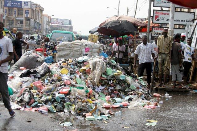 People walk past a pile of garbage along Ahmadu Bello Way in Kaduna, Nigeria October 29, 2015. (Photo by Reuters/Stringer)