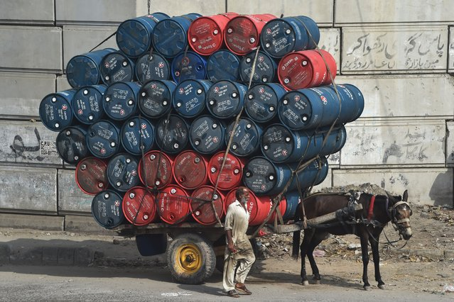 A man stands next to a horsecart laden with oil drums on a street in Lahore on September 27, 2020. (Photo by Arif Ali/AFP Photo)