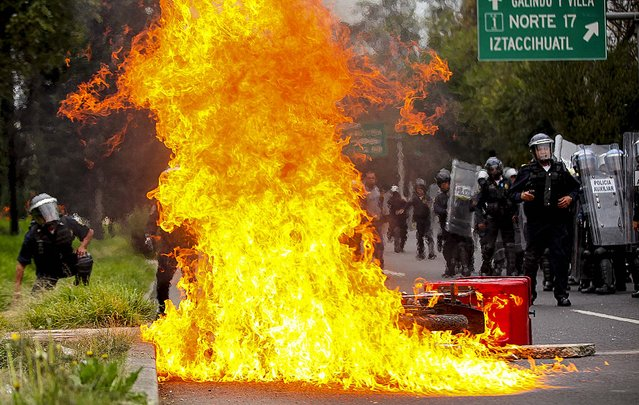A motorcycle burns after protesters threw molotov cocktails at riot police near the airport in Mexico City,Thursday, November 20, 2014. Mexico City is bracing for demonstrations as caravans of students and family members of 43 missing college students converged on the capital after several days crisscrossing the country. (Photo by Marco Ugarte/AP Photo)