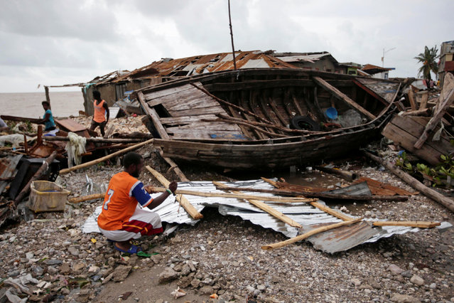 A man clears debris after Hurricane Matthew in Les Cayes, Haiti, October 5, 2016. (Photo by Andres Martinez Casares/Reuters)