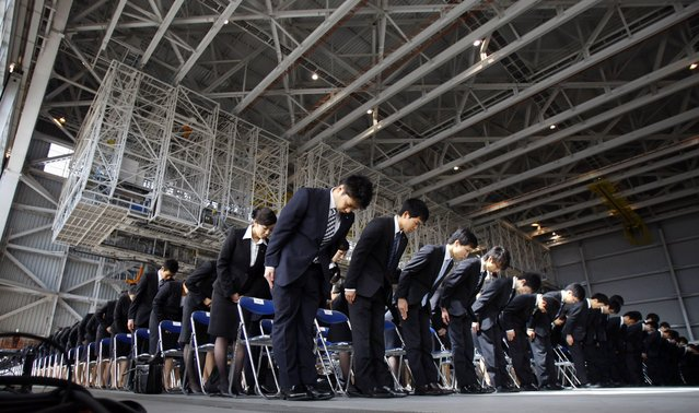 Newly hired employees of All Nippon Airways and ANA group companies bow during an initiation ceremony at the company's aircraft maintenance hangar at Haneda airport in Tokyo on Monday, April 1, 2013. A total 1,068 new recruits attended the ceremony. (Photo by Junji Kurokawa/AP Photo)