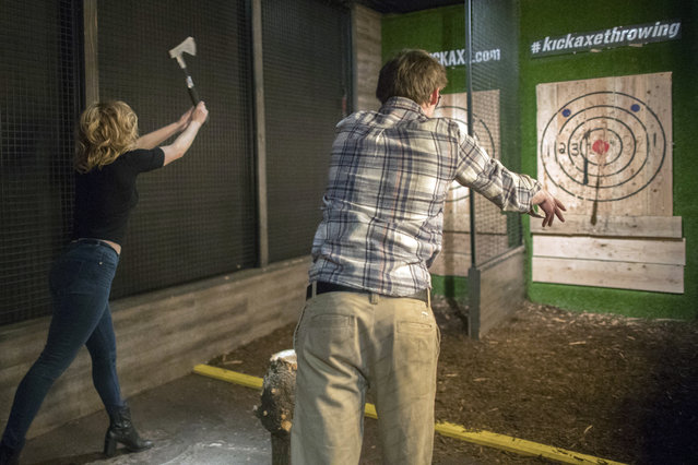 In this Saturday, March 3, 2018, photo, contestants throw hatchets at wooden bull's-eyes at the Kick Axe Throwing venue in the Brooklyn borough of New York. (Photo by Mary Altaffer/AP Photo)