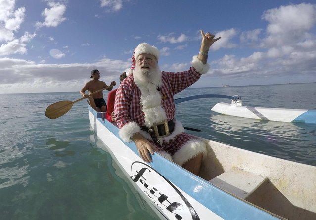 Donald Boyce, dressed up like Santa Claus, waves to surfers as he goes outrigger canoe surfing off Waikiki beach in Honolulu, Hawaii December 13, 2014. (Photo by Hugh Gentry/Reuters)