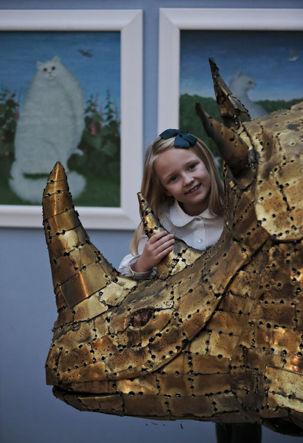 """A girl touches a bronze sculpture depicting a rhinoceros as she poses for the photographers during a press preview of a themed auction that features the animal as artistic inspiration, entitled the """"Creatures Great and Small"""", in London, Monday, December 15, 2014. (Photo by Lefteris Pitarakis/AP Photo)"""