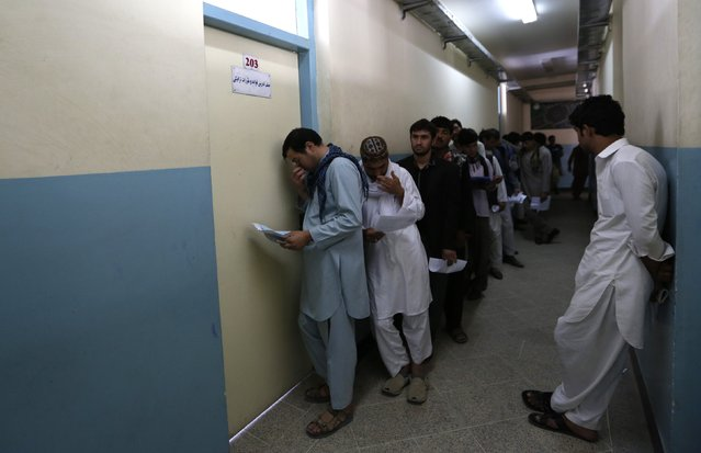 Afghan men line up as they wait for their turn to take a test before receiving a driving license at a traffic police department in Kabul August 23, 2014. (Photo by Mohammad Ismail/Reuters)