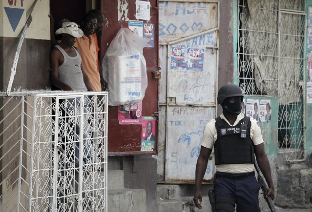 Residents look at a National Police officer as he controls the area after dispersing demonstrators protesting against the electoral process in Port-au-Prince, Haiti, November 6, 2015. Ruling party candidate Jovenel Moise and former government executive Jude Celestin led voting in Haiti's Oct. 25 presidential election and will face each other in a run-off next month, according to official results announced on Thursday. (Photo by Andres Martinez Casares/Reuters)
