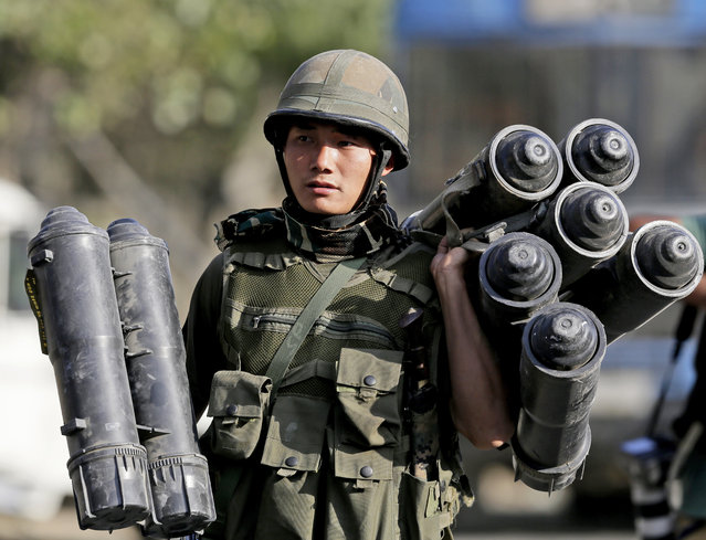An Indian Army soldier carries used ammunition boxes outside the government building where suspected militants had taken refuge during a gun battle in Pampore, on the outskirts of Srinagar, Indian controlled Kashmir, Wednesday, October 12, 2016. The Indian army says a three-day standoff between its soldiers and suspected rebels in Indian-controlled Kashmir has ended with the killing of two militants. (Photo by Mukhtar Khan/AP Photo)
