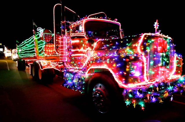 Participants in the annual Timber Truckers Light Parade head toward Myrtle Creek, Ore. from Riddle, Ore. Saturday December 13, 2014. (Photo by Michael Sullivan/AP Photos/The News-Review)