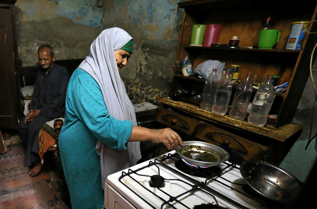 Saida Fathi Hassanein cooks lunch in her home in Ezbet Khairallah in Cairo, Egypt October 4, 2016. (Photo by Mohamed Abd El Ghany/Reuters)