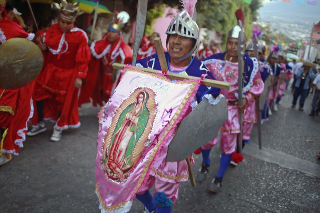 "Dancers performs with a banner of the Virgin of Guadalupe during the ""Paseo del Pendon"", a traditional artistic march in Chilpancingo, December 21, 2014. (Photo by Jorge Dan Lopez/Reuters)"