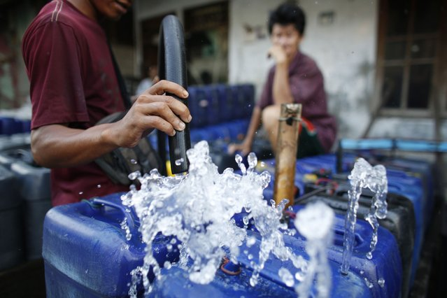 A man fills up his plastic containers with water before setting off to deliver them to residents who increasingly have no access to piped or well water in Pluit, north Jakarta, September 30, 2014. (Photo by Darren Whiteside/Reuters)
