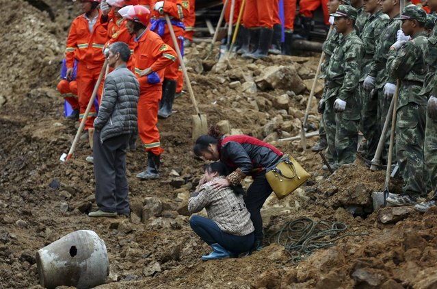 A woman (C) cries as rescuers search for survivors among debris at the site of a landslide in Yaxi township of Lishui, Zhejiang province, China, November 14, 2015. (Photo by Reuters/Stringer)