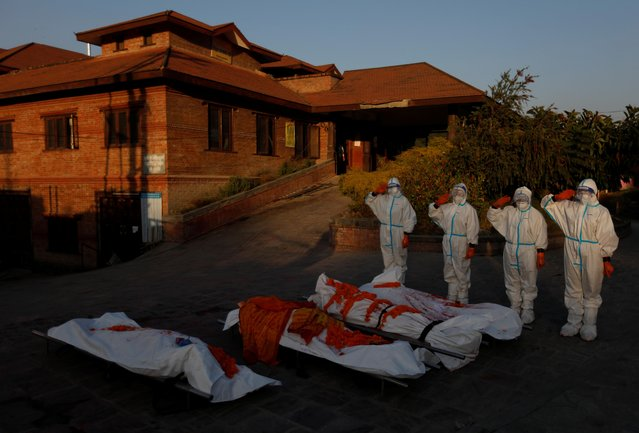 """Female soldiers pay tribute to the bodies of coronavirus victims at a crematorium in Kathmandu, Nepal, November 11, 2020. """"I feel privileged and happy for being given a chance to do the work that was done only by the males so far"""", said one of the women, a 25-year-old corporal named Rachana, who asked to be identified by just one name. """"Society is changing ... I have not been to my family since I started my new duty, but my friends are happy. They thank me and say, 'You have performed a difficult task carefully and maintained your personal safety. Thank you'. I feel happy"""". (Photo by Navesh Chitrakar/Reuters)"""