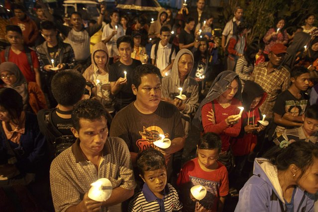 Indonesians hold up candles during a candle light vigil for the victims of AirAsia flight QZ8501 at Surabaya December 31, 2014. (Photo by Athit Perawongmetha/Reuters)