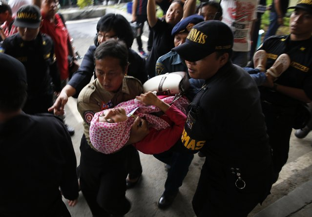 """Government security officials carry a family member of passengers onboard AirAsia flight QZ8501 after she collapsed at a waiting area in Juanda International Airport, Surabaya, December 30, 2014. Indonesian rescuers saw bodies and luggage off the coast of Borneo island on Tuesday and officials said they were """"95 percent sure"""" debris spotted in the sea was from a missing AirAsia plane with 162 people on board. (Photo by Reuters/Beawiharta)"""