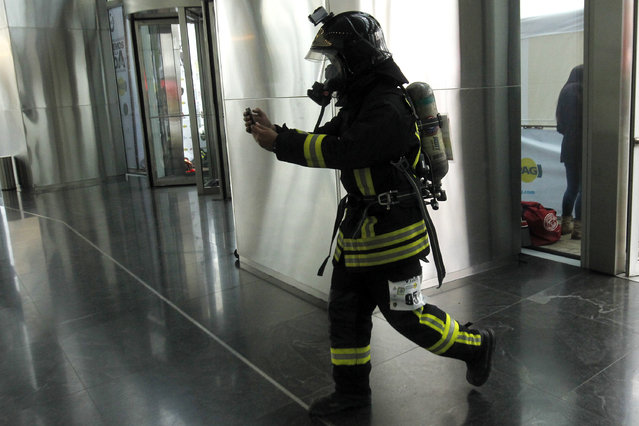 """A firefighter takes part in the """"Race for Life"""" at the Costanera Centre Tower aimed at encouraging organ donation in Chile, in Santiago, on October 16, 2016. (Photo by Claudio Reyes/AFP Photo)"""