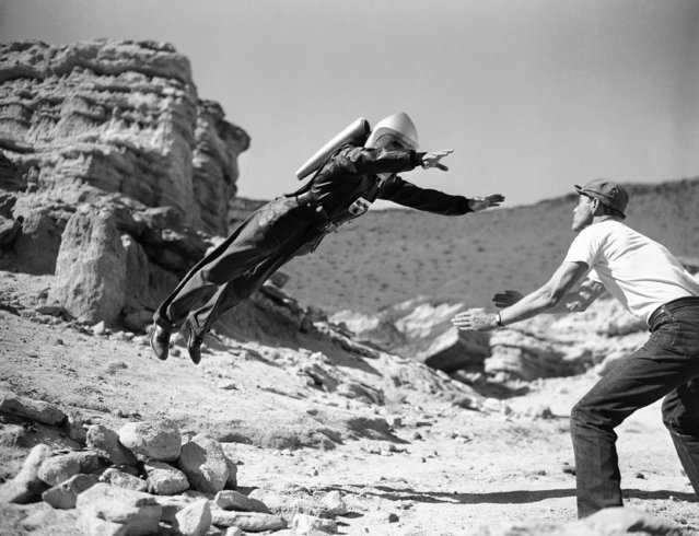 """Commando Cody, the Sky Marshal of the Universe"", aka, George Wallace, appears to defy the laws of gravity, for a moment at least, as he lands in the arms of a prop man during production of the film ""Radar Men from the Moon"", at Red Rock Canyon in the Mojave Desert, 80 miles northeast of Hollywood, Calif., December 12, 1951. Gravity may be defied in some the new movie serials based on the fantasies science fiction, but what goes up still comes down, even if the film wont let you see it. (Photo by AP Photo)"