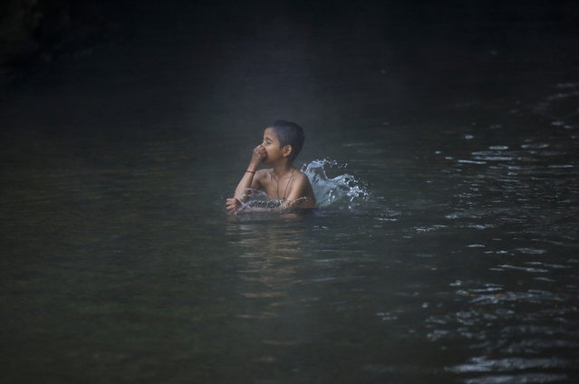 A boy takes a holy bath in the River Saali in Sankhu on the first day of Swasthani Brata Katha festival in Kathmandu January 5, 2015. (Photo by Navesh Chitrakar/Reuters)