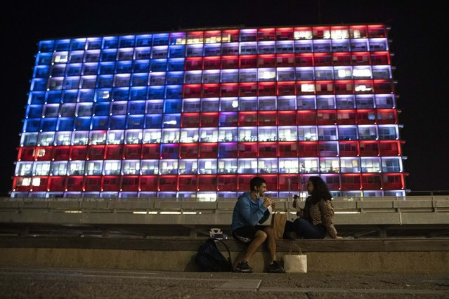 An Israeli couple sits near the Tel Aviv municipality building as it is lit up with the flag of the United States in Tel Aviv, Israel, Thursday, January 7, 2021. Officials said the display is a sign of solidarity with the United States and support for democracy. (Photo by Sebastian Scheiner/AP Photo)