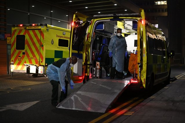 Paramedics tidy up an ambulance wearing PPE outside the Royal London hospital in London on January 10, 2021 as surging cases of the novel coronavirus are placing health services under increasing pressure. Medical chiefs in England raced to boost treatment capacity on January 10 as a surge in coronavirus cases risked overwhelming hospitals, even as the government stepped up its mass inoculation campaign. A leaked briefing suggested that London's hospitals were on the brink of running out of beds, endangering the lives of patients needing critical care. (Photo by Daniel Leal-Olivas/AFP Photo)