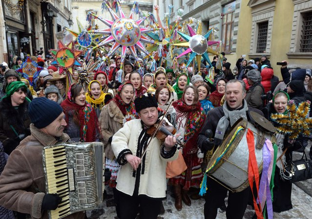 People, wearing traditional Ukrainian clothes, sing folk songs as they celebrate Orthodox Christmas in the western Ukrainian city of Lviv on January 8, 2015. (Photo by Yuriy Dyachyshyn/AFP Photo)