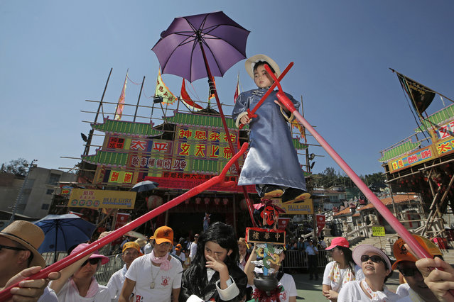 A child dressed in a traditional Chinese costume floats in the air, supported by a rig of hidden metal rods, during a parade on the outlying Cheung Chau island in Hong Kong to celebrate the Bun Festival Tuesday, May 22, 2018. (Photo by Kin Cheung/AP Photo)