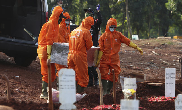 Workers in protective suits carry the coffin of a suspected victim of COVID-19 during a burial at Pondok Ranggon cemetery in Jakarta, Indonesia, Friday, June 12, 2020. (Photo by Achmad Ibrahim/AP Photo)