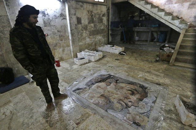 Raad, 37, inspects his mosaic artwork in a workshop in Kafranbel town in the Idlib governorate January 17, 2015. (Photo by Khalil Ashawi/Reuters)