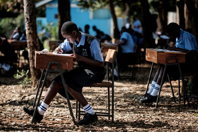 Students of St Dominic Bukna Secondary school take their English test outside due to their overcrowded class room in Kisumu, Kenya, on May 31, 2018. (Photo by Yasuyoshi Chiba/AFP Photo)