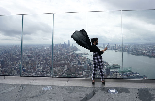 Anissa Barbato from New York looks out over the city as she takes pictures from the Edge, the highest outdoor sky deck in the Western Hemisphere on September 2, 2020 as it reopened to the public in New York. Rising 1,131 feet in the air from the heart of Hudson Yards it offers  360-degree views of New York Citys iconic skyline from the 100th floor outdoor viewing. (Photo by Timothy A. Clary/AFP Photo)