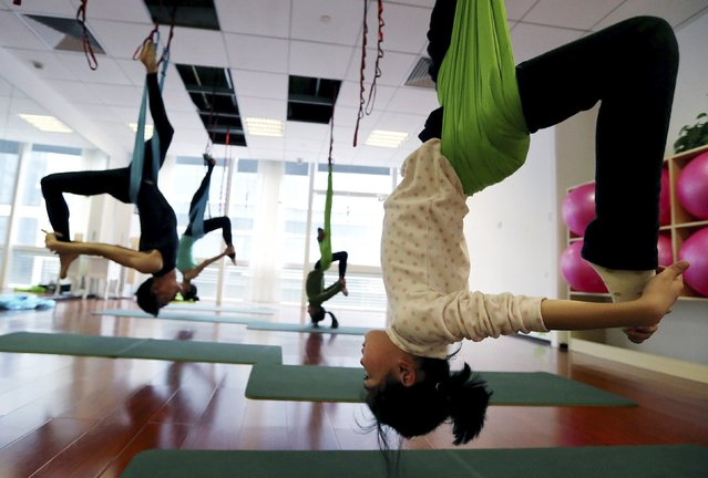 Students practice antigravity yoga at a training room in Hangzhou, Zhejiang province, January 11, 2015. (Photo by Reuters/Stringer)