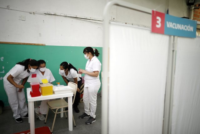 Nurses read instructions for injecting doses of the Sputnik V COVID-19 vaccine at a Bernal public school, on the outskirts of Buenos Aires, Argentina, Thursday, February 18, 2021, as the country begins to vaccinate healthcare workers against the new coronavirus. (Photo by Natacha Pisarenko/AP Photo)