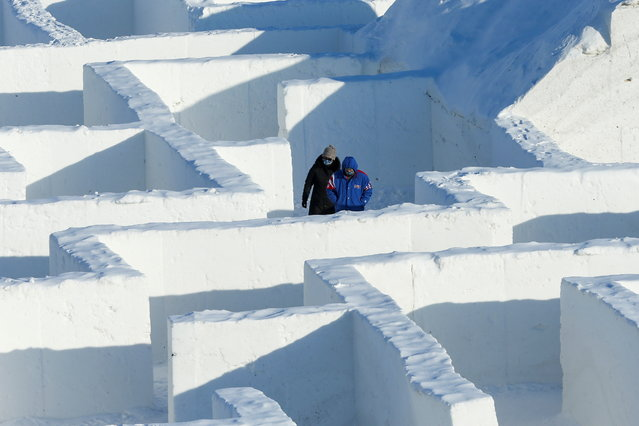 People navigate through a giant snow maze, even larger than a similar maze build on the same site in 2019, which was proclaimed the world's largest by Guinness World Records, in St. Adolphe, Manitoba, Canada on February 19, 2021. (Photo by Shannon VanRaes/Reuters)