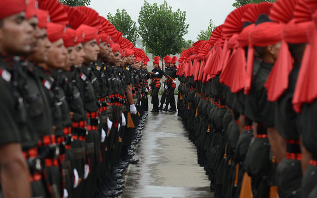 Recruits from the Jammu and Kashmir Light Infantry Regiment (JAKLI) of the Indian Army take part in a passing out parade in Srinagar on July 10, 2013. The 494 recruits, many of them locals, completed a 49-week training programme prior to being absorbed as regular members of the regiment. (Photo by Tauseef Mustafa/AFP Photo)