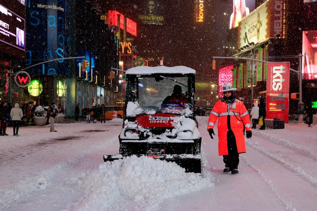 A plow is driven through Times Square on January 26, 2015 in New York City. New York, and much of the Northeast, is bracing for a major winter storm which is expected to bring blizzard conditions and 10 to 30 inches of snow to the area. (Photo by Alex Trautwig/AFP Photo)