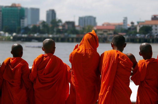 Buddhist monks look on at the start of a boat race near the Royal Palace during the annual Water Festival on the Tonle Sap river in Phnom Penh, Cambodia November 14, 2016. (Photo by Samrang Pring/Reuters)