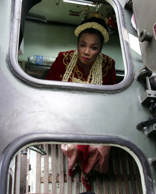 A bride looks out of an Indonesian Army vehicle during a mass wedding ceremony in Jakarta, Indonesia, Wednesday, January 28, 2015. (Photo by Achmad Ibrahim/AP Photo)