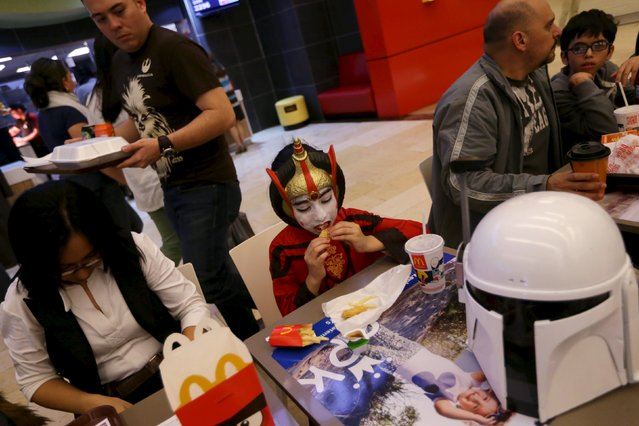"""A girl dressed as a character from Star Wars eats during an event held for the release of the film """"Star Wars: The Force Awakens"""" at a movie theater in Guatemala City, December 16, 2015. (Photo by Jorge Dan Lopez/Reuters)"""